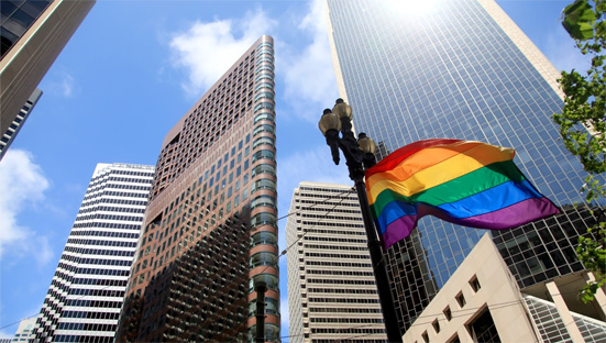 A rainbow flag flying outdoors, in front of skyscrapers