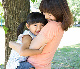 Smiling mother and daughter hugging outdoors