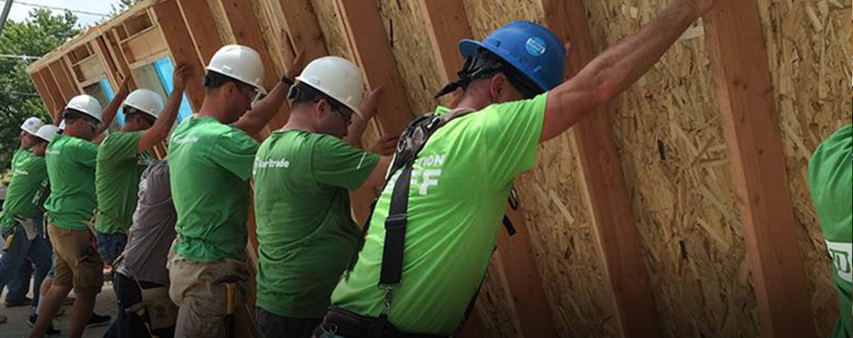 A group of TD Ameritrade volunteers putting up a house frame together