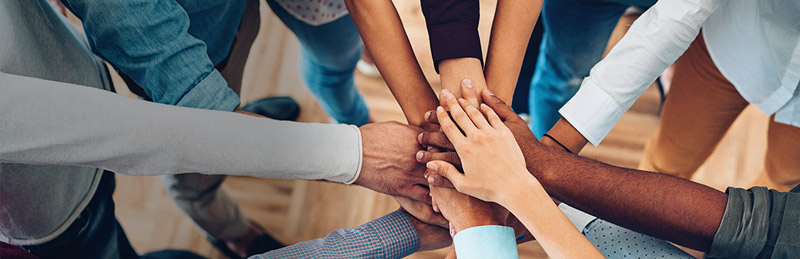 Many people's hands of varying skin tones, stacked on top of one another in a team-building cheer