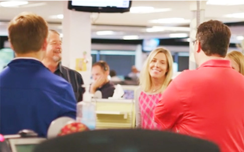 Four employees casually meeting in an open office, smiling