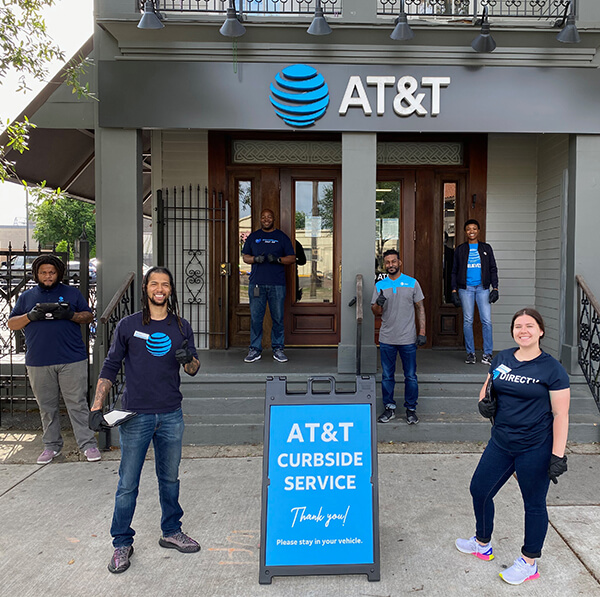 Employees smiling outside of an AT&T store providing curbside service.