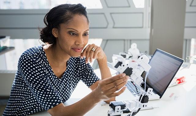 Young woman examining robotic arm at desk