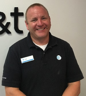 Tedd smiling with the AT&T logo behind him