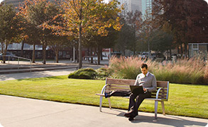 Man sitting in park, using laptop