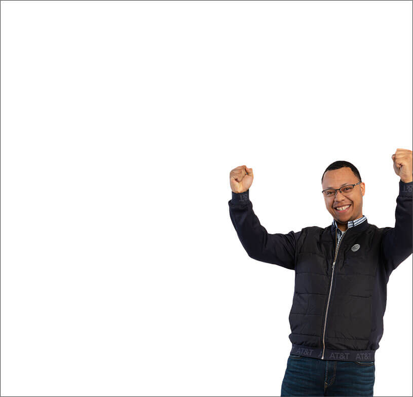 Male employee with arms in air and smiling