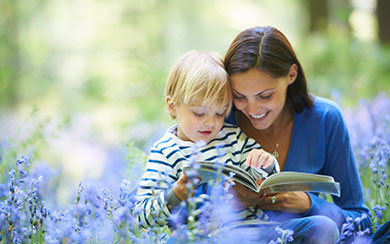 Mom reading book to son outside in a field of flowers