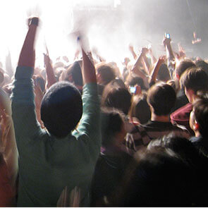 Crowd of people cheering at a concert