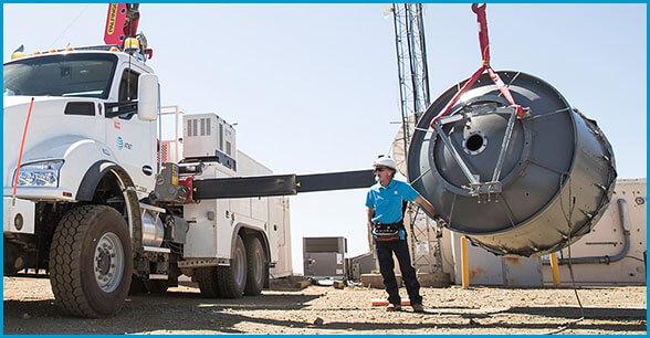 Technician loading big piece of equipment onto truck