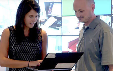 Two employees looking at a laptop screen