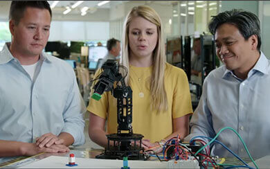 Three employees looking at some robotics work