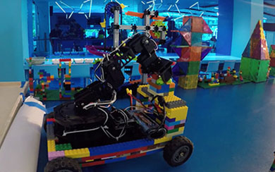 Motorized lego vehicle with robotic arm attached