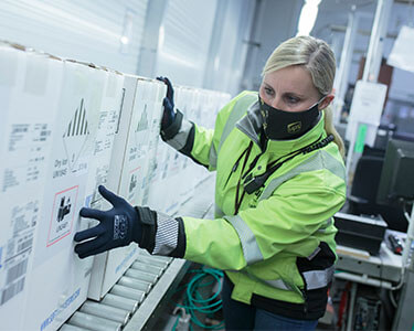 Woman focused on job, putting large boxes on conveyor belt