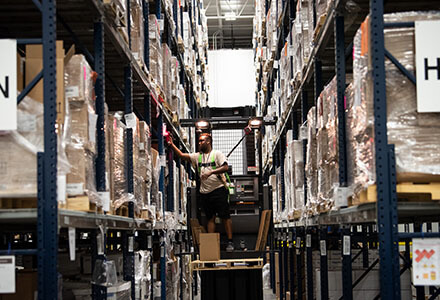 Man standing on lift, working in a large warehouse