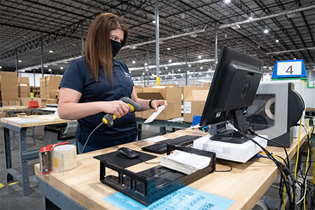 Woman scanning item and looking at computer screen