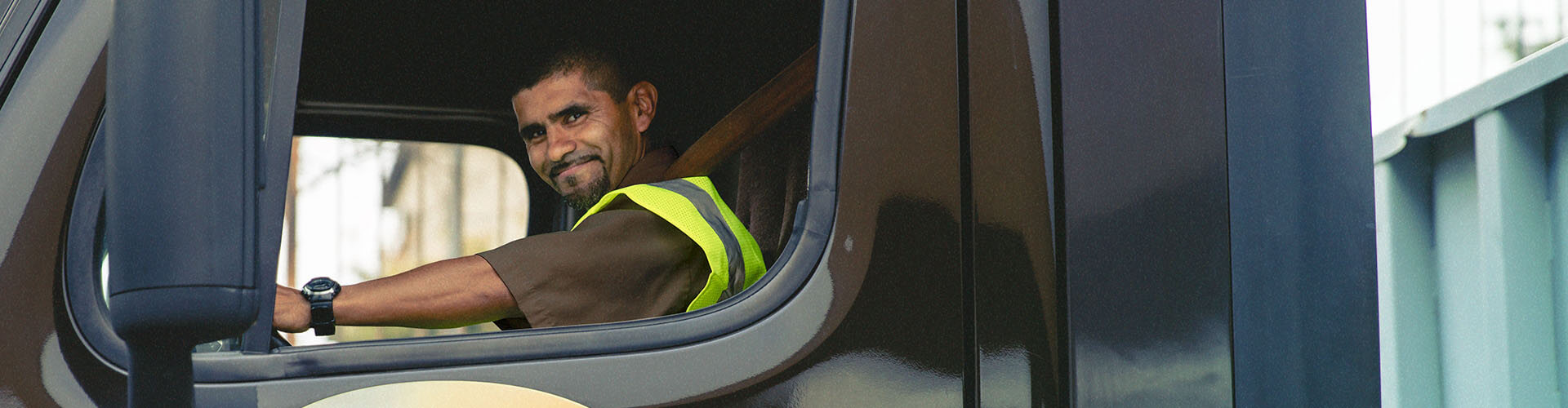 Man smiling while sitting in semi truck