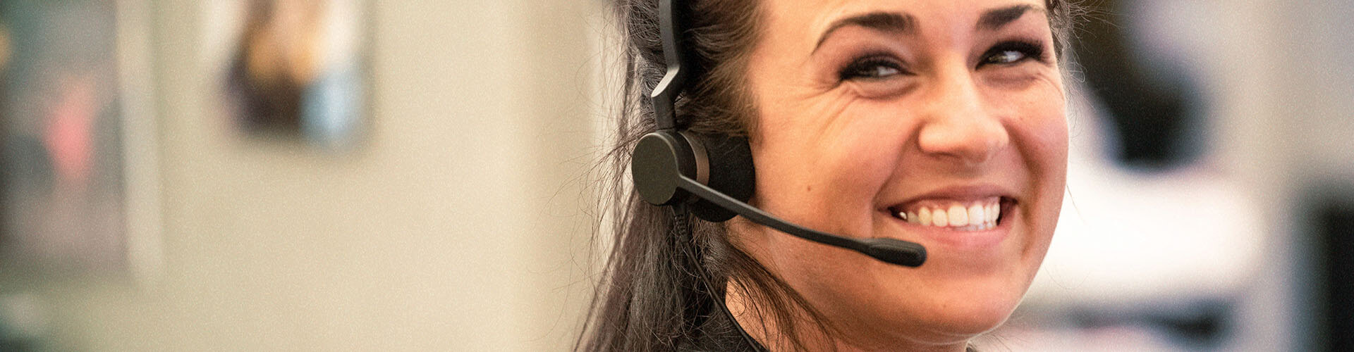 Woman with a big smile, and is wearing a headset