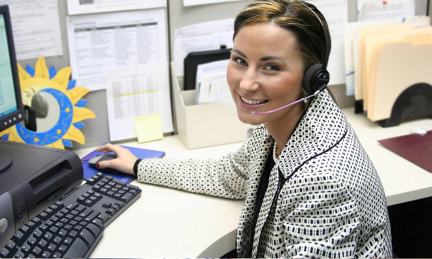 A nurse smiling and using a headset to make a phone call
