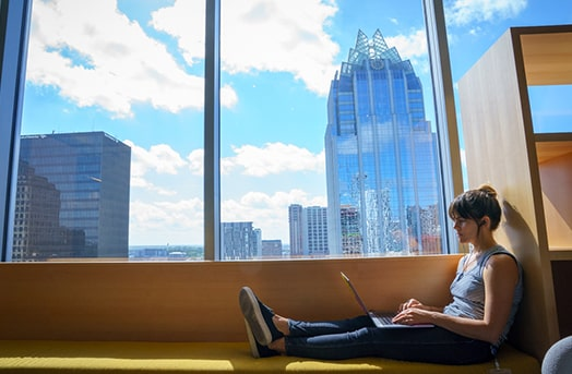 Woman sitting on the floor working on her laptop with a city skyline on display in the window above her