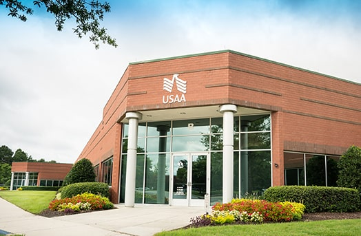 A stucco fronted building with high glass panels showing the entrance to the USAA office in Chesapeake, Virginia