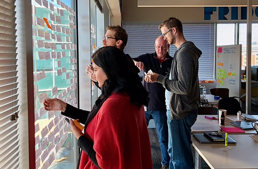 Group of people placing post it notes on windows and working together in an office