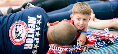 A man with a TAPS Mentor logo on back of t-shirt, laying down next to and facing a little boy.