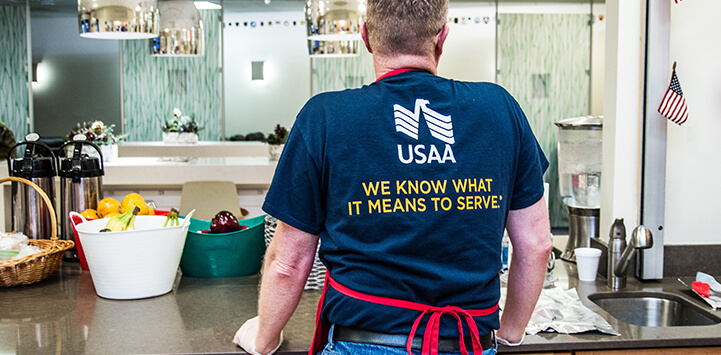 A USAA worker is standing with a shirt that reads 'We know what it means to serve'