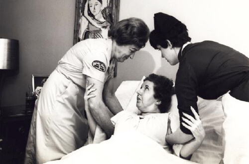Two nurses help lift a patient in 1950