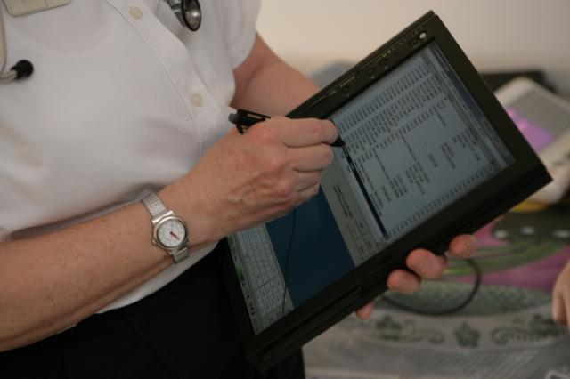 A nurse useing an old tablet from the early 90's