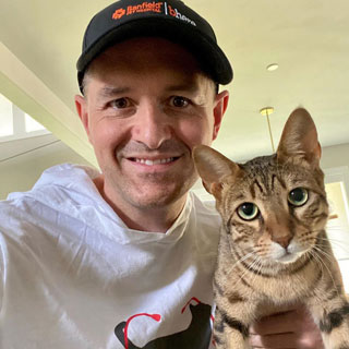 Thumbnail: A person wearing cap and holding a cat with him