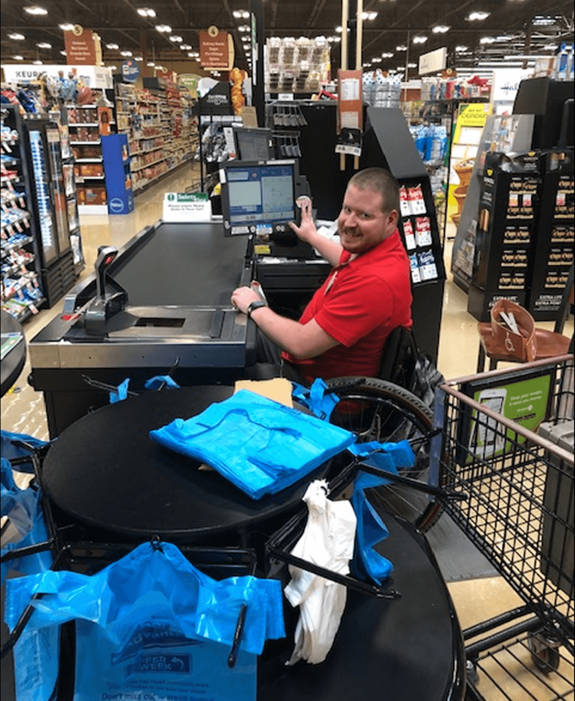 Travis in wheelchair working cash register