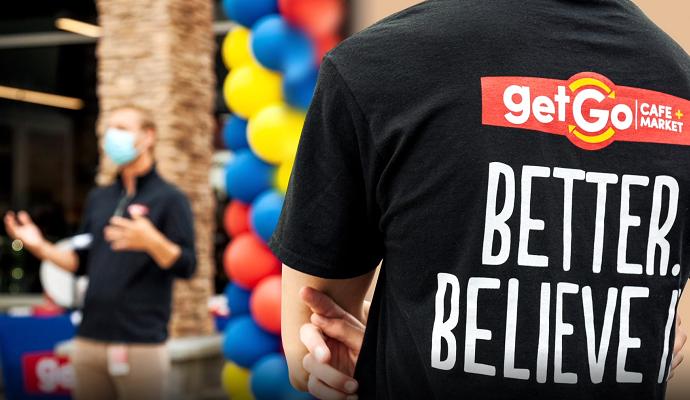 """在新店开业典礼上,穿着""""Get Go""""衬衫的男人看到另一个男人讲话"""