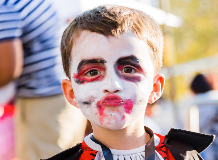 Little boy in a vampire costume with his face painted puckering his lips
