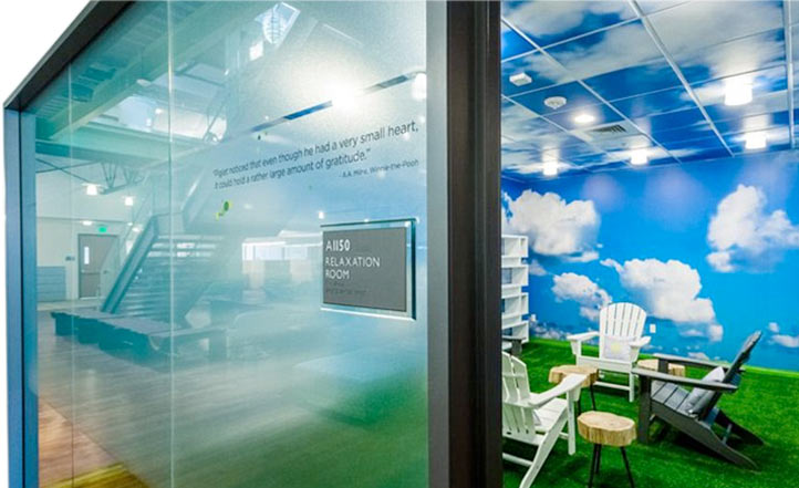 A peek into a glass enclosed, outdoor-looking meeting room with blue walls with clouds on them and green grass-like carpet