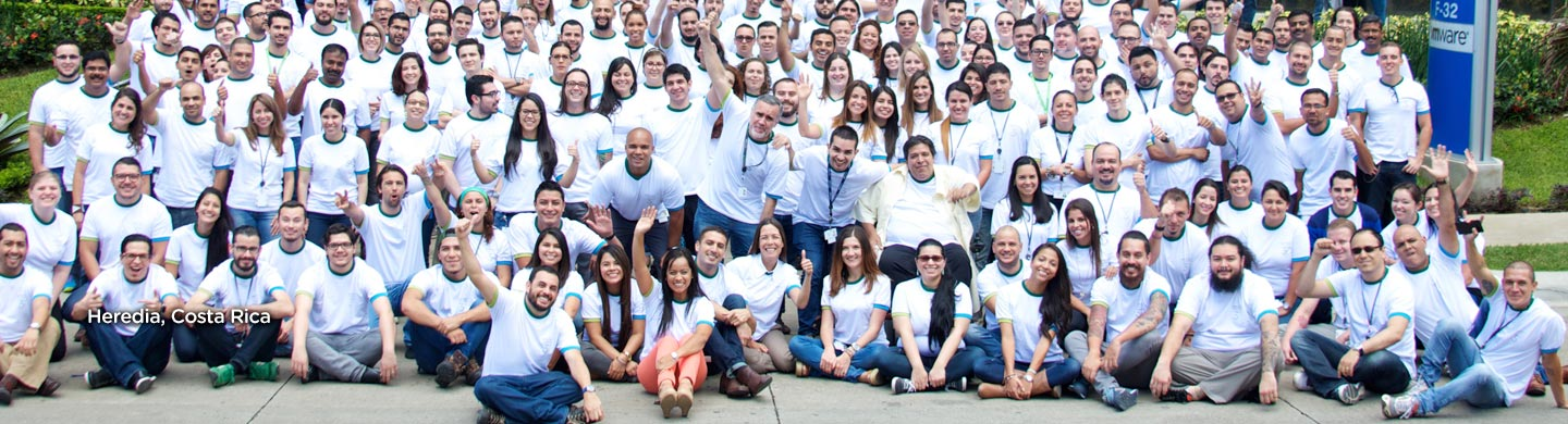 Big group of employees in while shirts smiling in Heredia, Costa Rica.