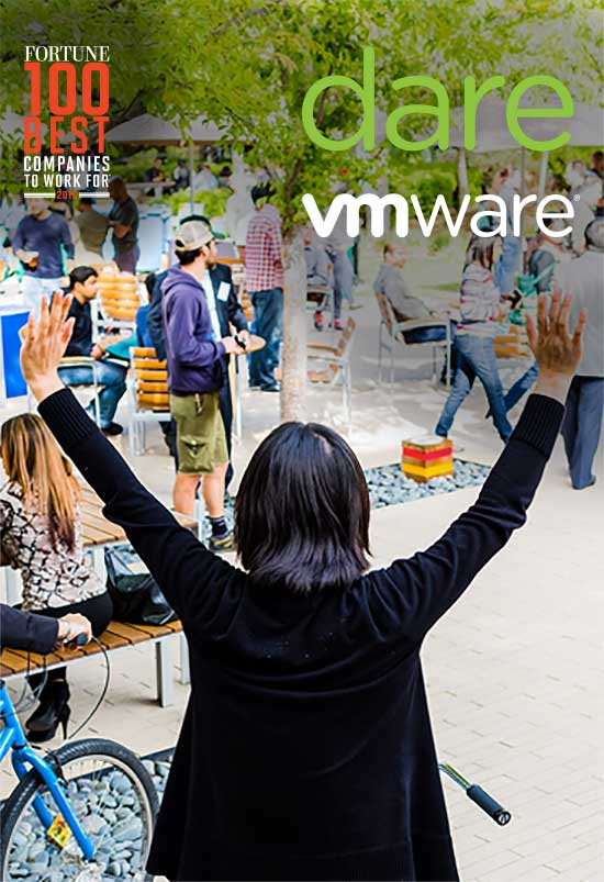 Woman on bike raises hands in air in celebration, during a busy lunch hour outside on VMware's campus.