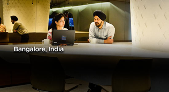 Man in sits next to woman on her computer in Bangalore, India office.