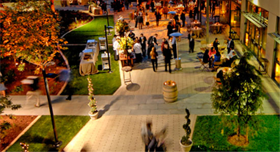 Aerial view of people gathering on VMware's tree-filled campus during an event.