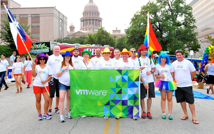 Employees with colorful hats and VMware banner hold Texas and rainbow flags at a pride parade in Texas.