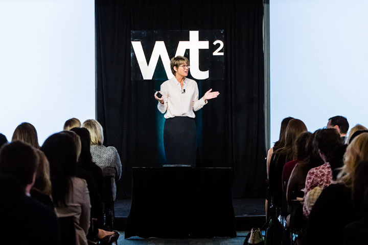 Woman speaks in front of an audience at the WT2 event.