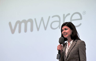 Woman speaks with microphone in front of VMware logo.
