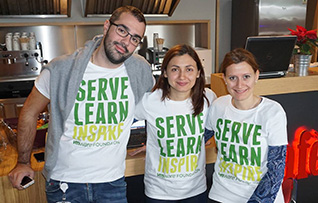 Three employees in service learning t-shirts smile for a photo.