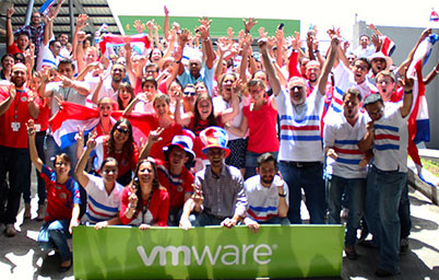 Big group of employees in red, white, and blue raise their arms in celebration