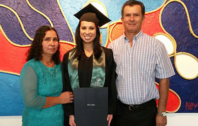 Girl in cap and gown smiles next to her parents.
