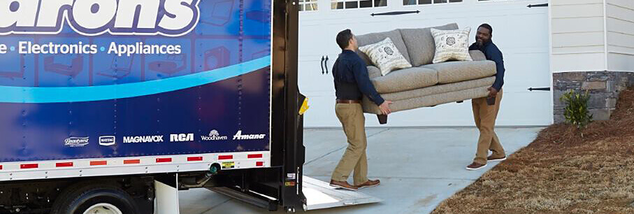 Two drivers delivering a sofa to a customer