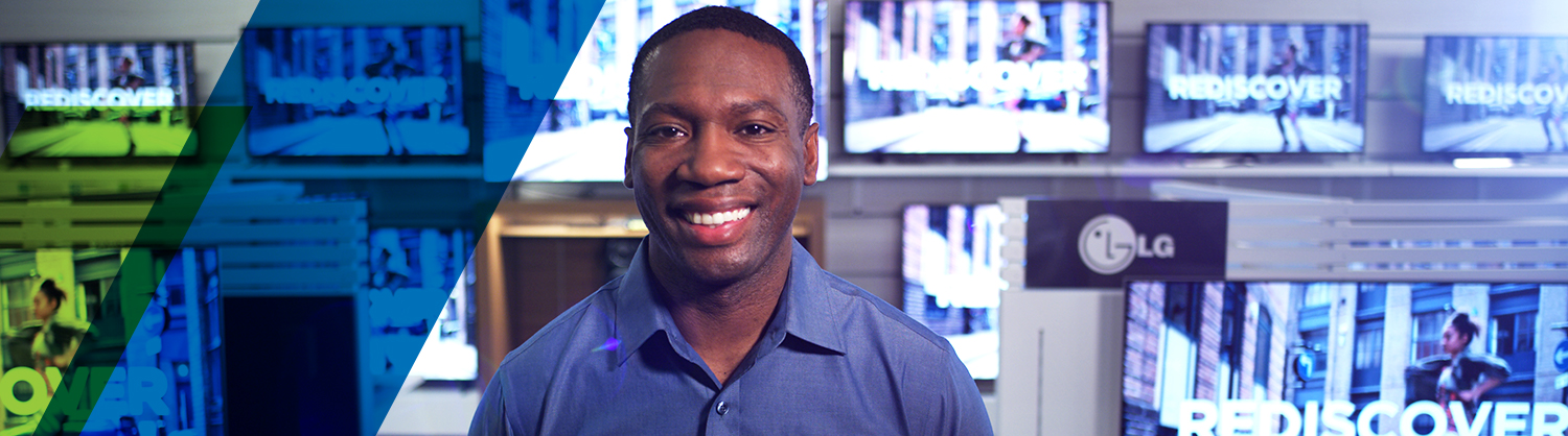 Black man smiling wearing dark blue denim shirt