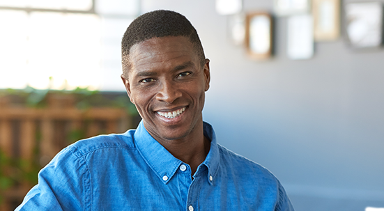Black man smiling wearing blue shirt