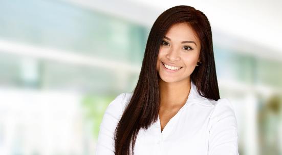 Woman with long dark hair smiling wearing white blouse