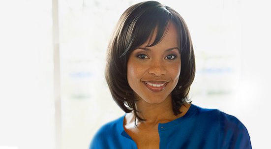 Black woman with dark mid-neck length hair smiling wearing blue blouse