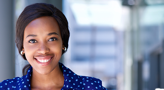 Black woman with dark short cropped hair smiling wearing polka dot blouse